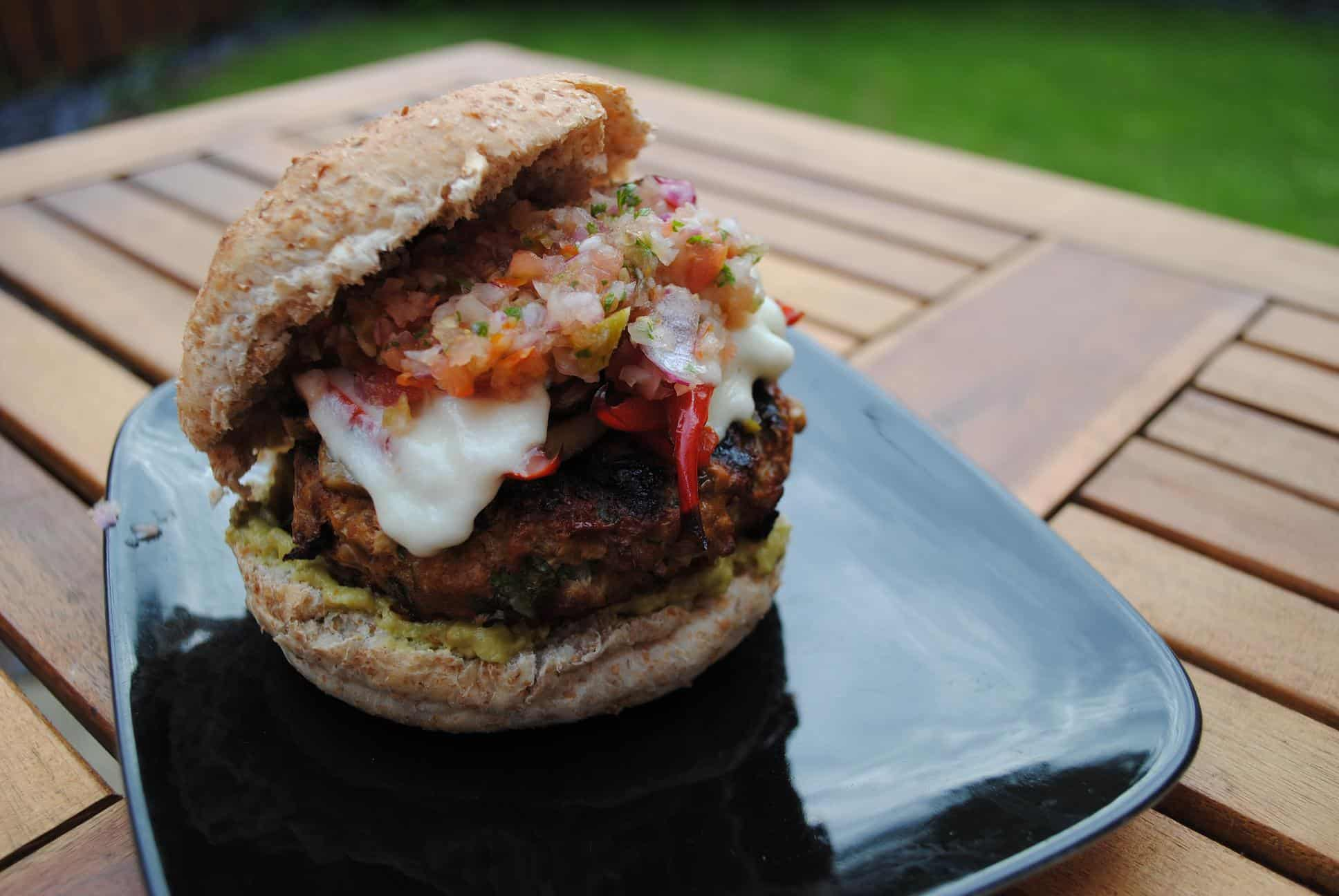Mexican burger on a black plate on a wooden table