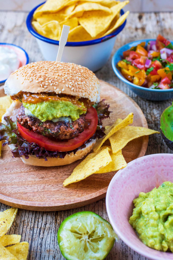 A Mexican Burger in a sesame seed bun with tomato and guacamole