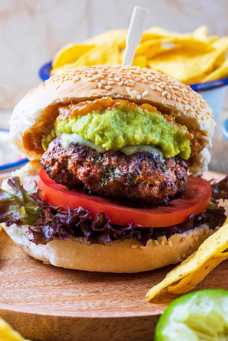 Mexican burger in a bun with sliced tomato, lettuce and avocado