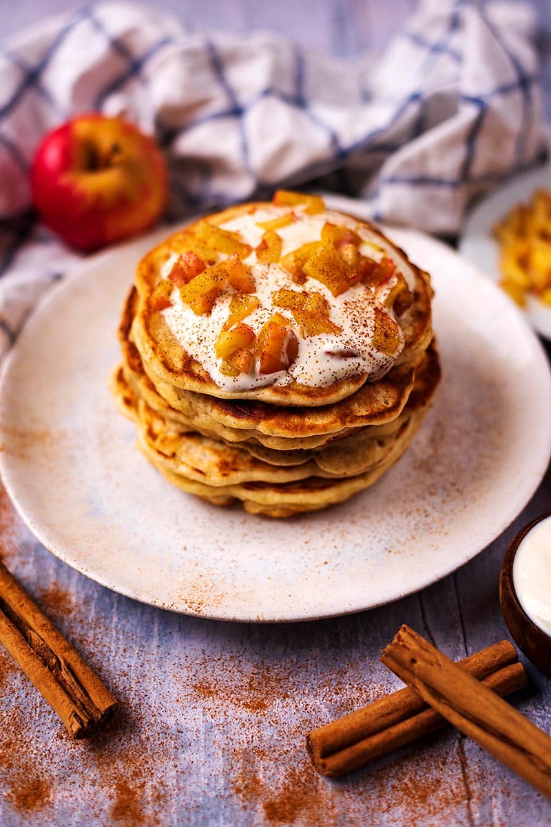 A stack of apple and cinnamon pancakes topped with yogurt and diced apple