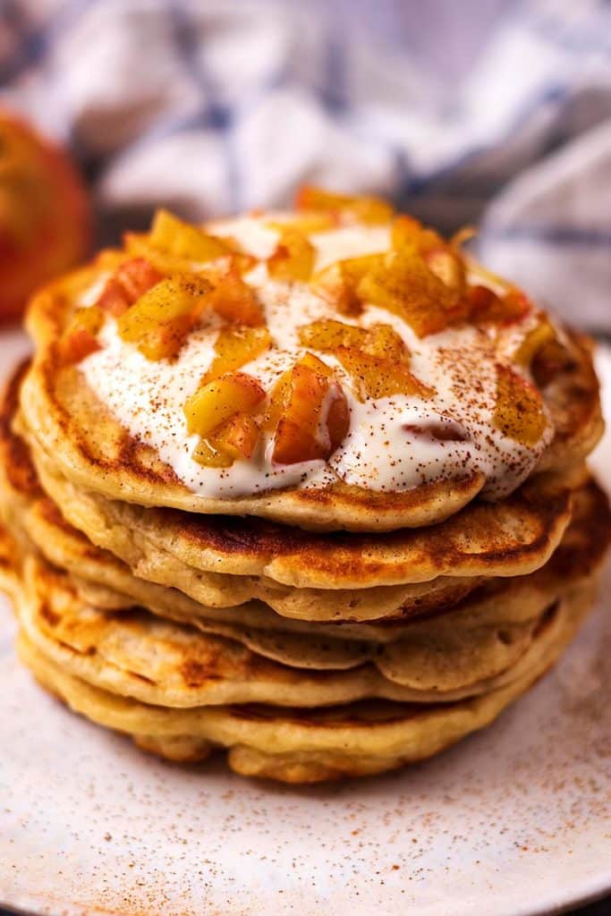 Six apple and cinnamon pancakes in a stack topped with yogurt and apples