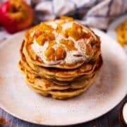 A stack of Apple and Cinnamon Pancakes next to some apples