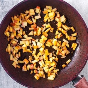 A frying pan with diced apple cooking in it