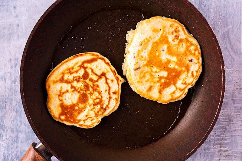 A frying pan with two pancakes being cooked in it