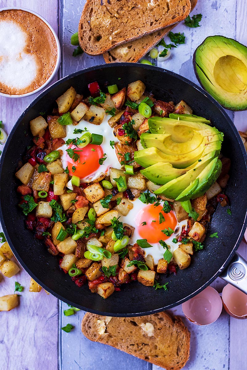 A pan of breakfast hash next to toast, coffee and an avocado
