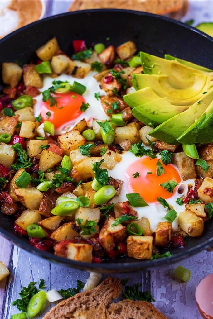 Breakfast hash in a frying pan topped with sliced avocado