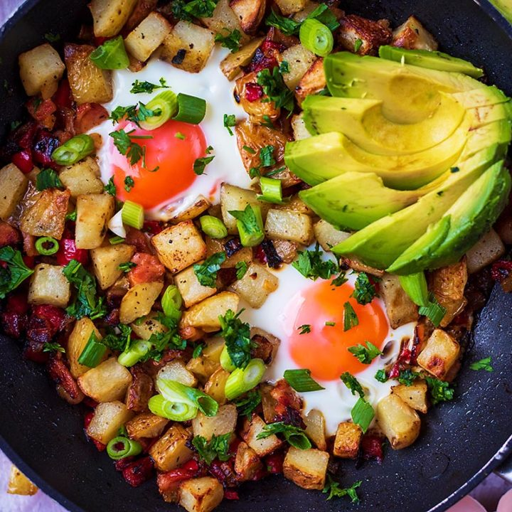 Breakfast Hash in a frying pan with sliced avocado