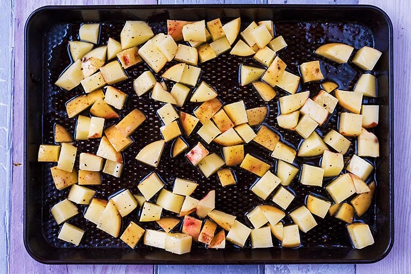 A baking tray with cubes of potato on it