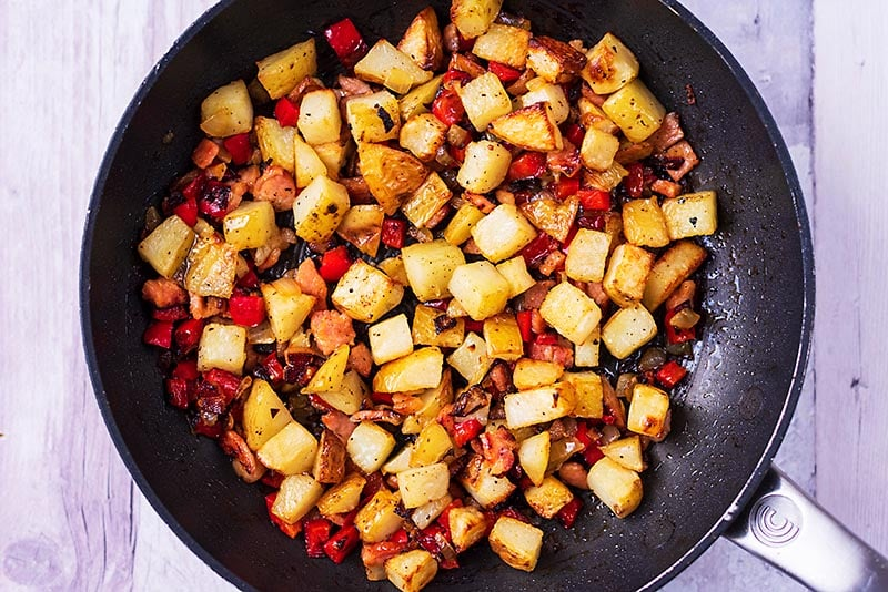 A frying pan with cubed potatoes, vegetables, bacon and spices cooking in it
