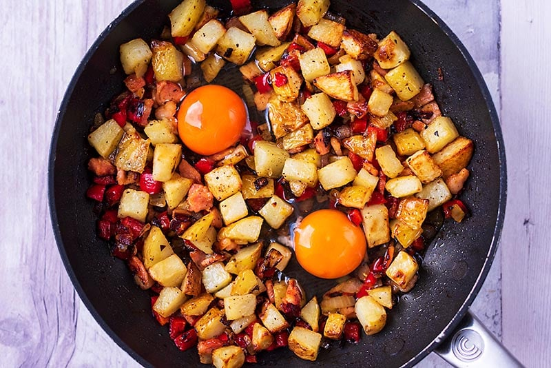 A frying pan with breakfast hash and two uncooked eggs in it