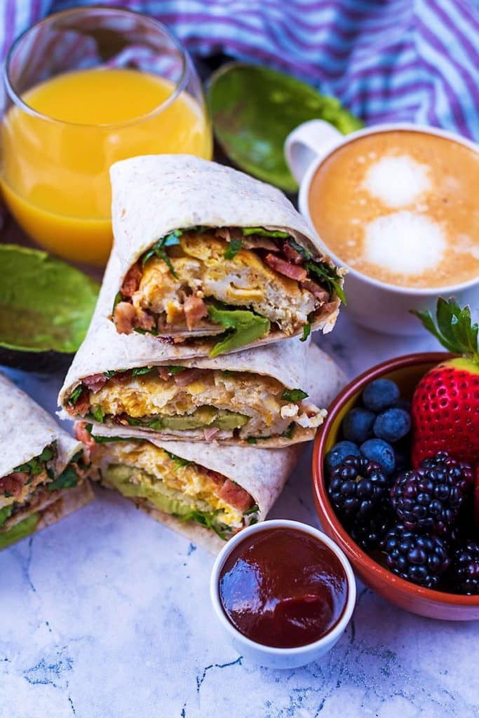 Three breakfast wraps piled up with a bowl of fruit and a cup of coffee