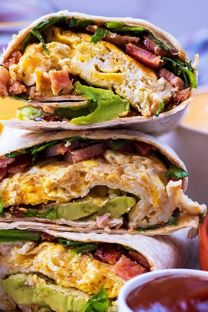 Breakfast wraps showing egg, bacon, avocado and spinach