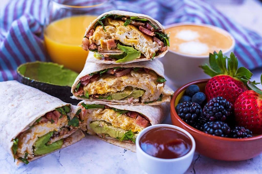 A stack of three Breakfast wraps piled next to a bowl of berries