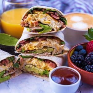 A stack of three breakfast wraps next to a bowl of berries, a cup of coffee and a glass of orange juice