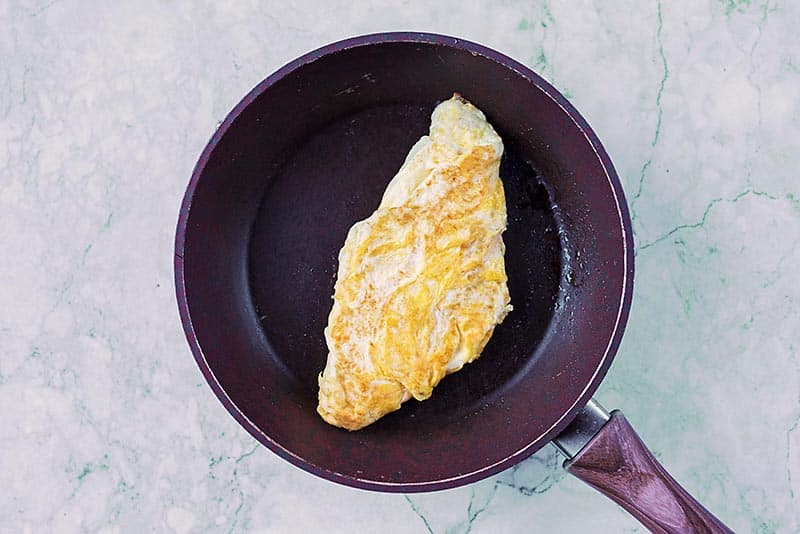 A frying pan with a folded omelette in it