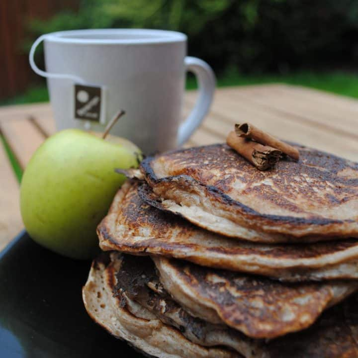 Apple Cinnamon Pancakes on a plate with an apple and a cup of tea
