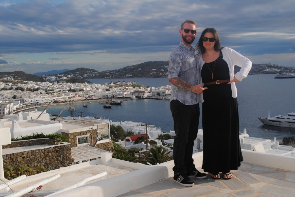 Dave and Dannii stood on a rooftop overlooking a harbour. Both are pointing to Dannii's stomach