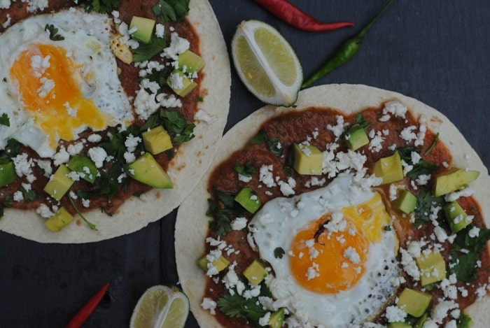 Huevos Rancheros on a slate surface with lime wedges
