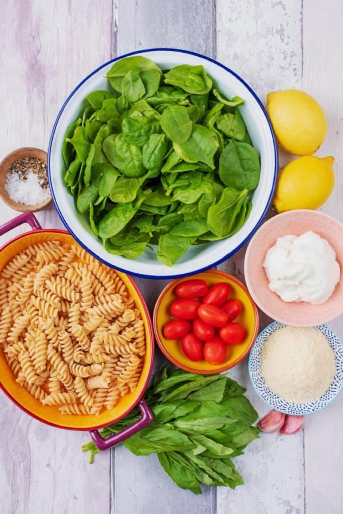 Pasta, spinach, tomatoes, lemons, yoghurt, herbs and spices on a wooden surface