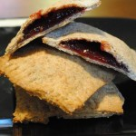 Hoomemade Poptart cut open on other poptarts on a black plate