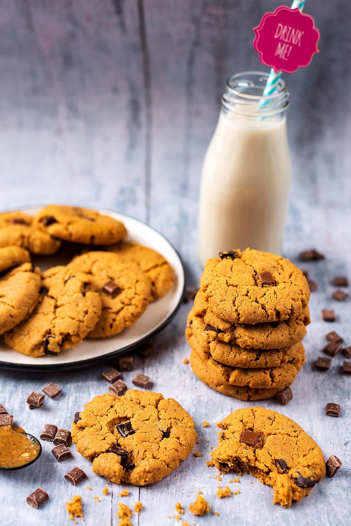A plate of chocolate chip cookies next to a stack of more cookies and a bottle of milk