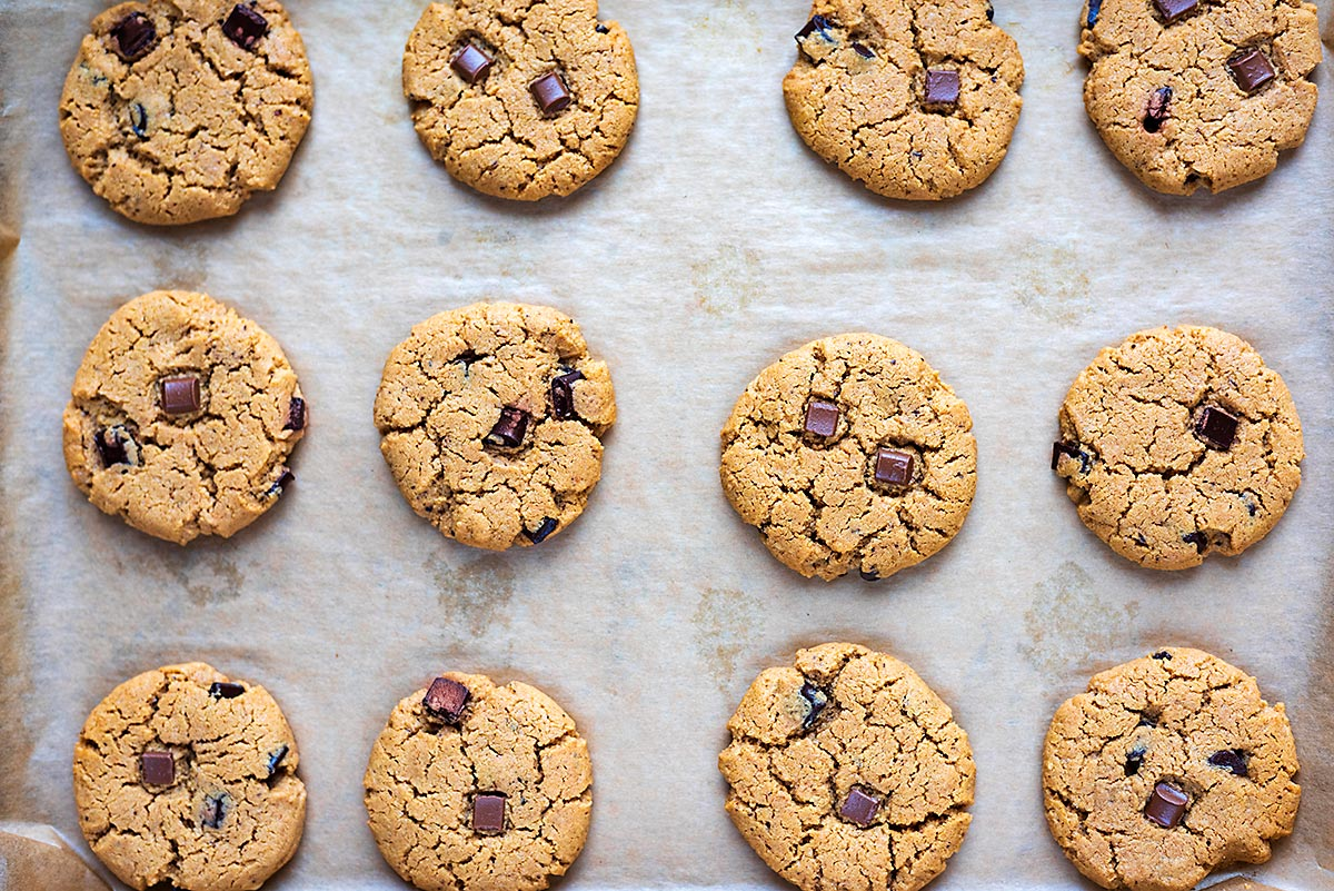 A lined baking tray with twelve baked chocolate chip cookies