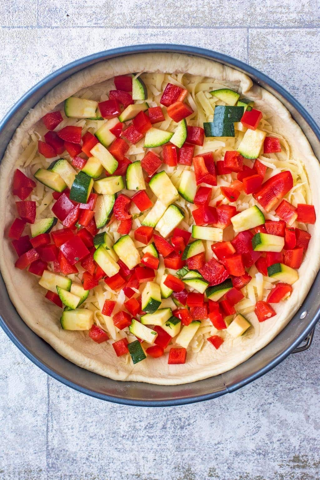 Deep Dish Pizza tin with pizza dough, cheese and vegetables