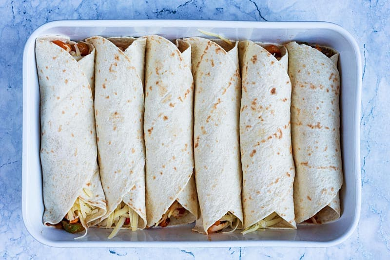 Six rolled up enchiladas in a baking dish