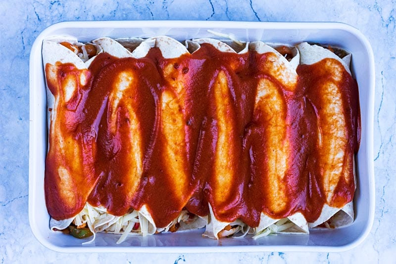 A baking dish with six enchiladas covered in sauce