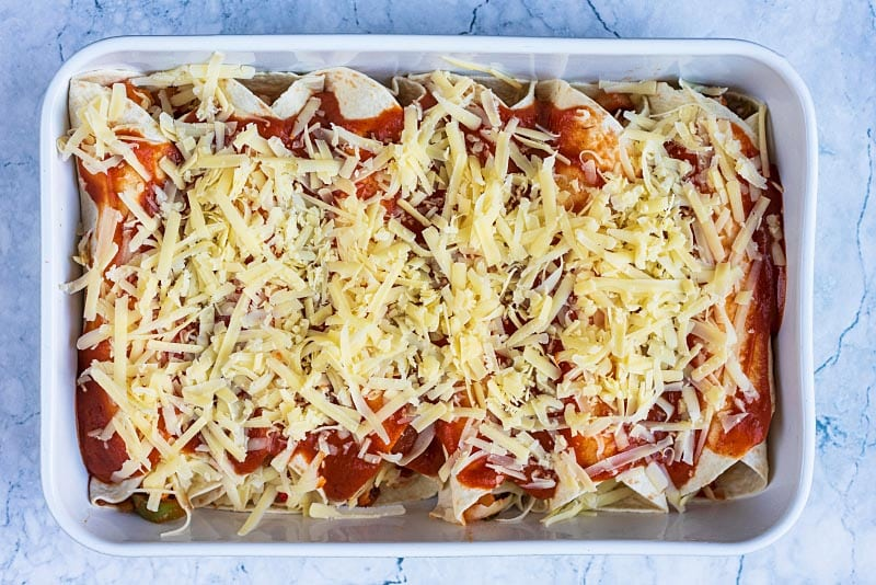 Enchiladas in a baking dish covered in sauce and cheese