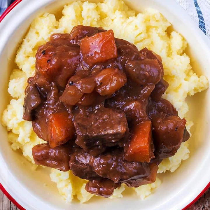Slow Cooker Beef Casserole and mashed potato in a white dish
