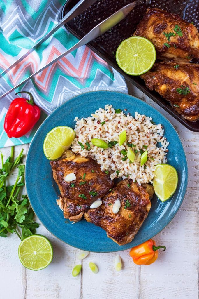 A plate of slow cooker jerk chicken with rice and limes. Scotch bonnet peppers and coriander leaves are next to the plate