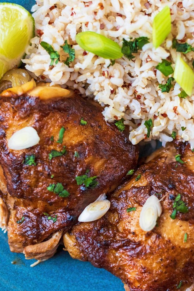 Jerk chicken thighs and rice topped with sliced scallions on a blue plate