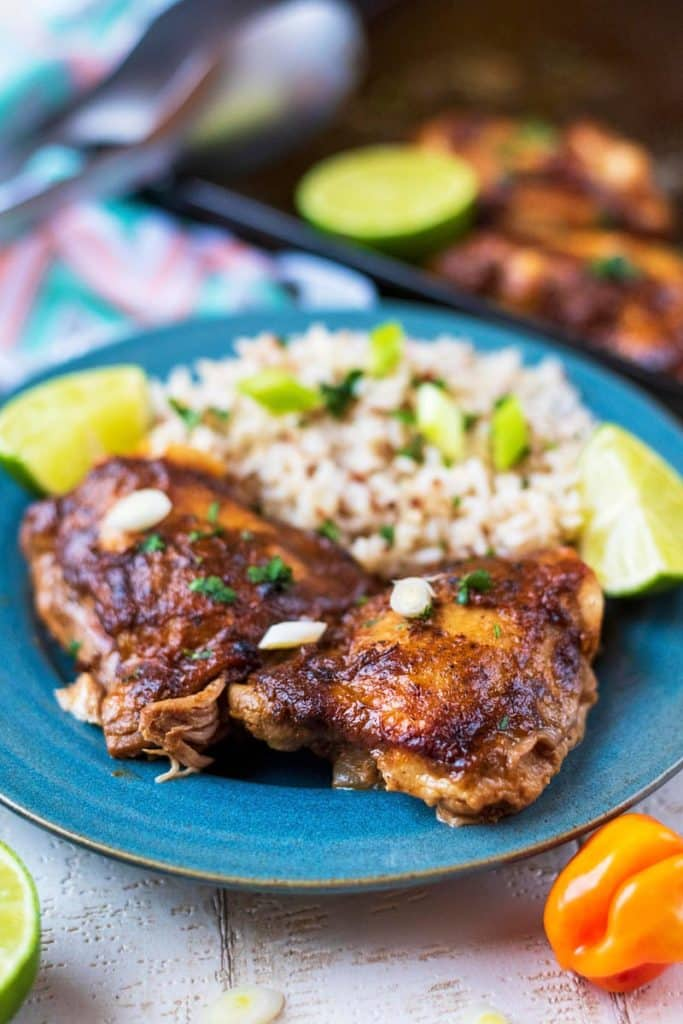 Cooked chicken in a jerk coating on a plate with rice. A pan of chicken is in the background