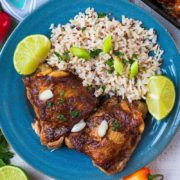 Two slow cooker jerk chicken thighs on a blue plate with rice and lime wedges