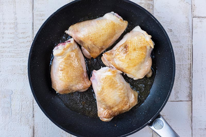 A frying pan with four chicken thighs in it