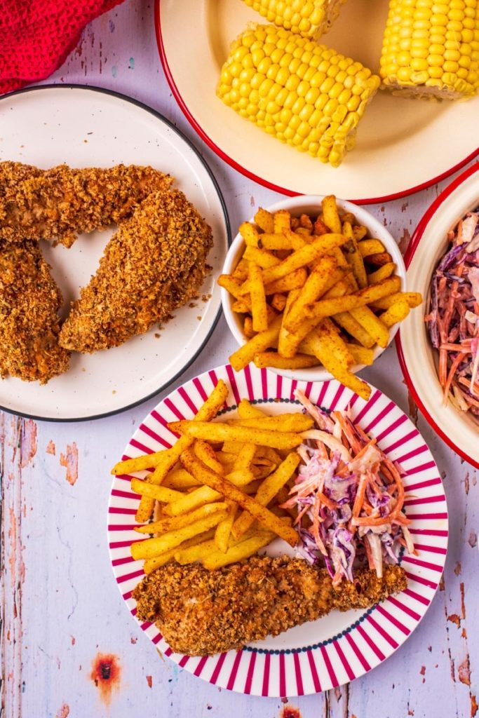 Healthy KFC on plates next to fries, coleslaw and corn on the cob