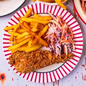 A piece of Healthy KFC on a plate with fries and slaw