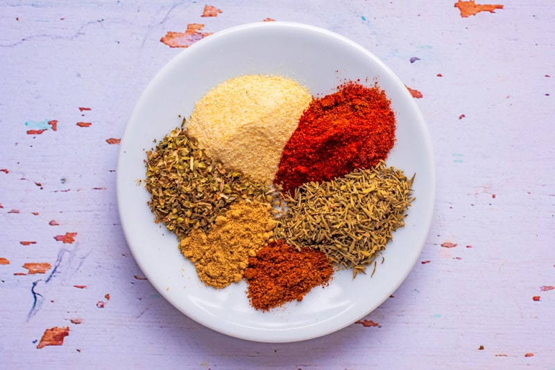 A white plate with six small piles of spices
