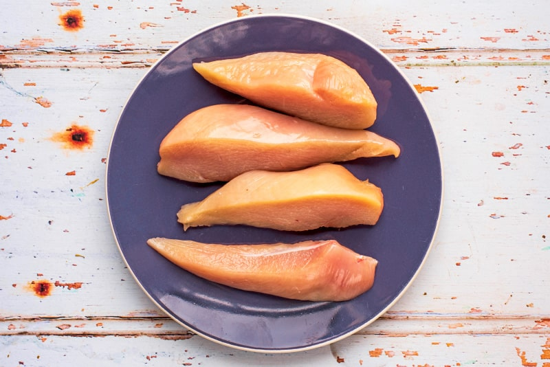 A blue plate with raw chicken breast cut into four long strips