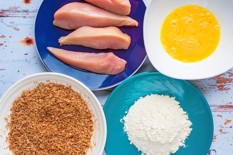 A plate with raw chicken breast strips, a plate with white flour, a bowl with seasoned breadcrumbs and a bowl with whisked egg