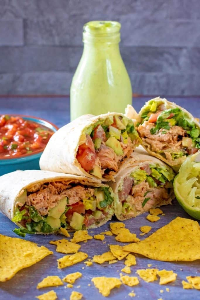 Sliced salmon burritos with some crumbled tortilla chips