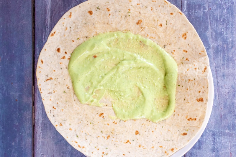 A tortilla wrap with a green coloured sauce spread over it