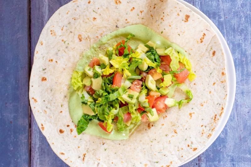 A tortilla wrap with green sauce and chopped salad