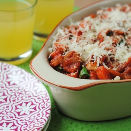 Eggplant Parmesan in an oval dish with two orange drinks