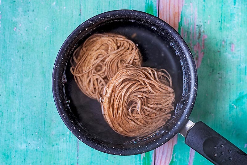 A saucepan containing two nests of wholewheat noodles
