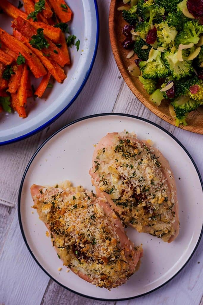 Two stuffed chicken breasts on a plate next to plates of carrots and broccoli