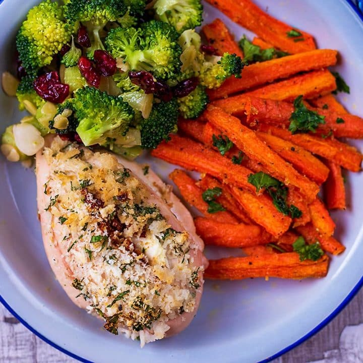 A stuffed chicken breast on a plate with carrots and broccoli