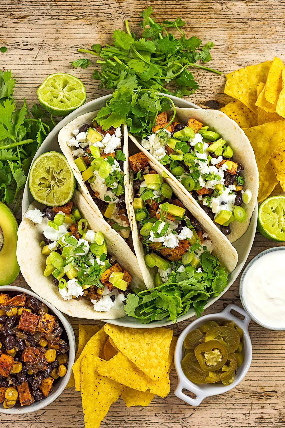 A serving bowl containing four tacos topped with chopped onions, avocado and feta.