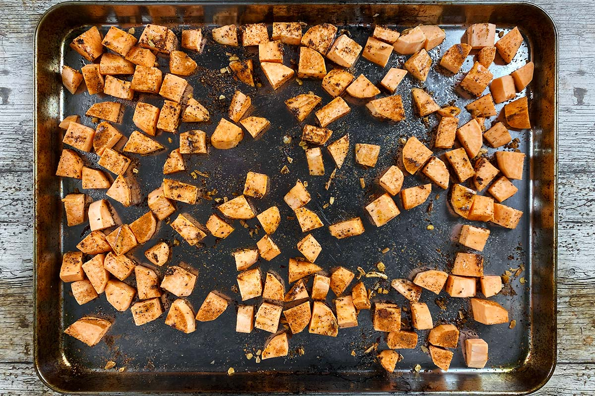 A baking tray with cubes of sweet potato spread over it.